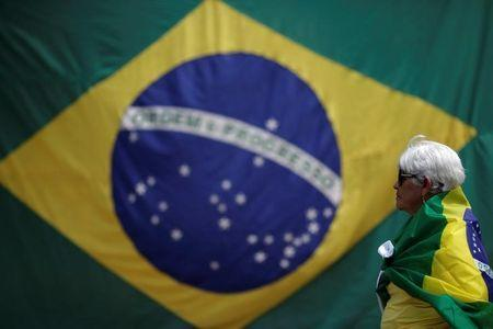 A woman is seen with a Brazilian flag in front of the National Congress during a protest against corruption, in Brasilia