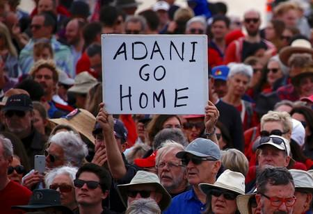 FILE PHOTO: A protester holds a sign as he participates in a national Day of Action against the Indian mining company Adani's planned coal mine project in north-east Australia, at Sydney's Bondi Beach in Australia