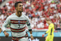 """FILE - In this Tuesday, June 15, 2021 file photo Portugal's Cristiano Ronaldo celebrates after scoring his second team goal during the Euro 2020 soccer championship group F match between Hungary and Portugal at the Ferenc Puskas stadium in Budapest, Hungary. Video from the game showed Hungarian fans chanting """"Cristiano homosexual!"""" at Portuguese captain Cristiano Ronaldo during the match. In 2017, FIFA, soccer's international governing body, fined the Hungarian Football Federation $22,000 after Hungarian fans directed the same chant at Ronaldo at a World Cup qualifier in Budapest. (Bernadett Szabo/Pool via AP, File)"""