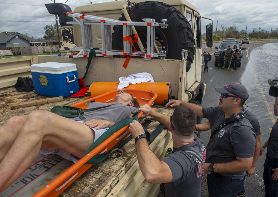 St. John the Baptist Parish rescue teams place a person onto the back of a truck during an evacuation on the morning after Hurricane Ida hit the area, Monday, Aug. 30, 2021, in St. John the Baptist Parish, La. (Chris Granger/The Times-Picayune/The New Orleans Advocate via AP)