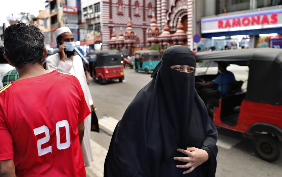 A burqa clad Sri Lankan Muslim woman walks in a street of Colombo, Sri Lanka, Saturday, March 13, 2021. Sri Lanka on Saturday announced plans to ban the wearing of burqas and said it would close more than 1,000 Islamic schools known as madrassas, citing national security. (AP Photo/Eranga Jayawardena)