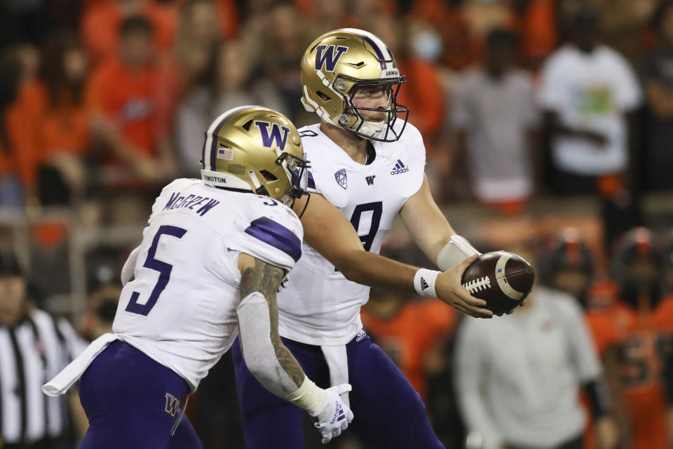 Washington quarterback Dylan Morris (9) hands off to running back Sean McGrew (5) during the first half of an NCAA college football game against Oregon State on Saturday, Oct. 2, 2021, in Corvallis, Ore. (AP Photo/Amanda Loman)
