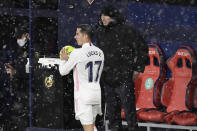 Real Madrid's head coach Zinedine Zidane, right, watches as Real Madrid's Lucas Vazquez prepares to take a throw-in during a Spanish La Liga soccer match between Osasuna and Real Madrid at El Sadar stadium in Pamplona, Spain, Saturday, Jan. 9, 2021. (AP Photo/Alvaro Barrientos)
