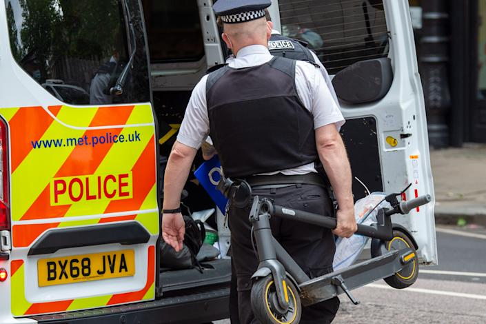 A police officer puts a confiscated electric scooter into a police van after having stopped a male for riding it in London. (PA)