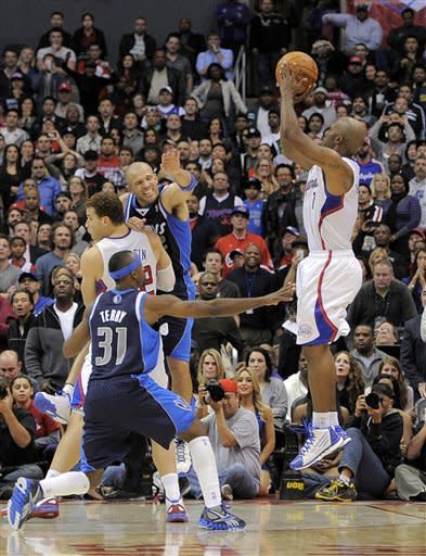 Los Angeles Clippers guard Chauncey Billups, right, shoots and hits a three point shot in the last few seconds of their NBA basketball game as Dallas Mavericks guard Jason Terry (31) defends along with guard Jason Kidd, center right, and Los Angeles Clippers forward Blake Griffin, top left,, Wednesday, Jan. 18, 2012, in Los Angeles. The Clippers won 91-89. (AP Photo/Mark J. Terrill)