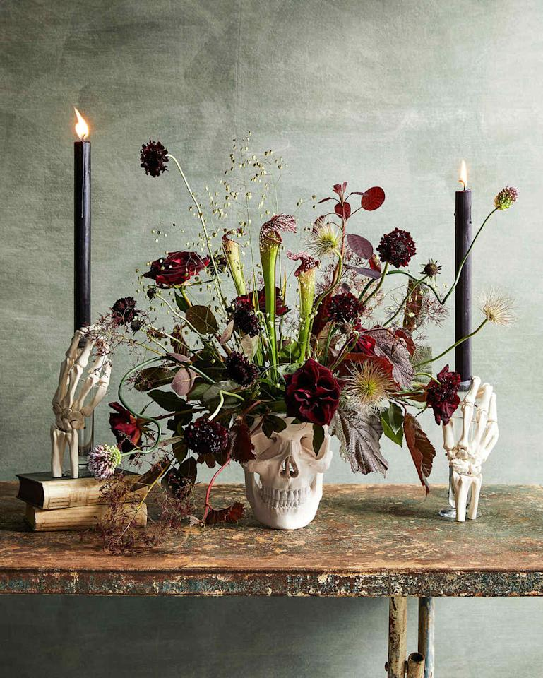 """<p>Gather your guests 'round the table <a href=""""https://www.marthastewart.com/275614/halloween-centerpieces-and-tabletop-idea"""">with this departed decorator as the centerpiece</a>.&nbsp;A grinning skull is brimming with seasonal blooms while&nbsp;two bony hands clutch at taper candles.</p>"""