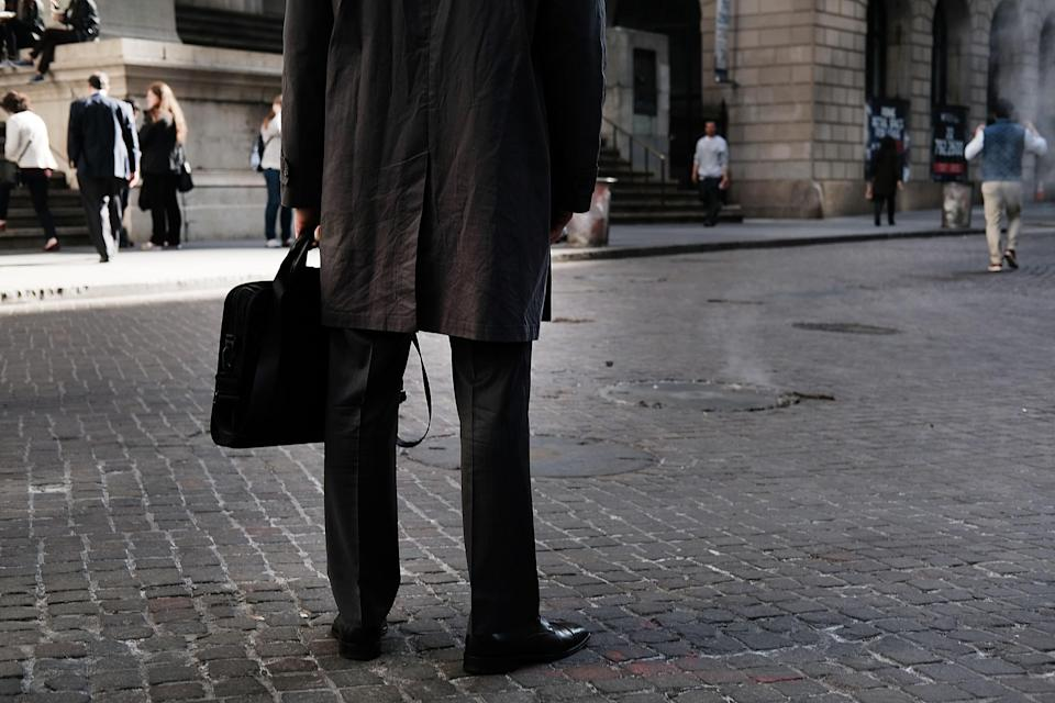 A man in a suit stands outside of the New York Stock Exchange.