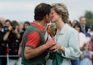 <p>A classic everyday jewelry pairing, Diana wore a gold watch and gold hoops to support Prince Charles at a 1985 charity polo match. </p>
