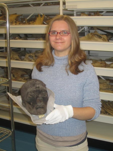 Researcher Alexandra Touzeau holding a mummy skull with its skin and hair still attached.