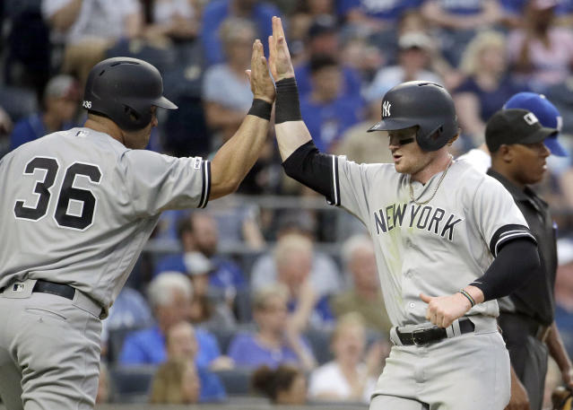 New York Yankees' Clint Frazier, right, and Kendrys Morales (36) celebrate after they scored on a single by Austin Romine during the second inning of the second baseball game in a doubleheader against the Kansas City Royals, Saturday, May 25, 2019, in Kansas City, Mo. (AP Photo/Charlie Riedel)