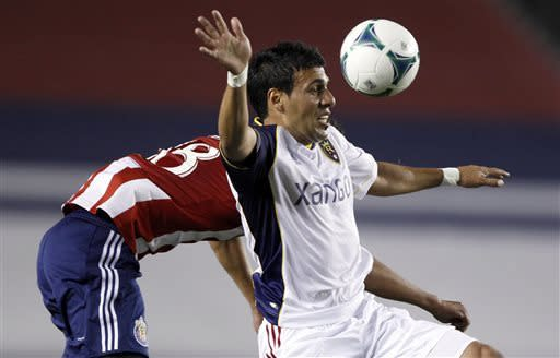 Real Salt Lake midfielder Javier Morales, right, controls the header against Chivas USA midfielder Martin Ponce for the ball during the first half of an MLS soccer game in Carson, Calif., Sunday, May 19, 2013. (AP Photo/Alex Gallardo)