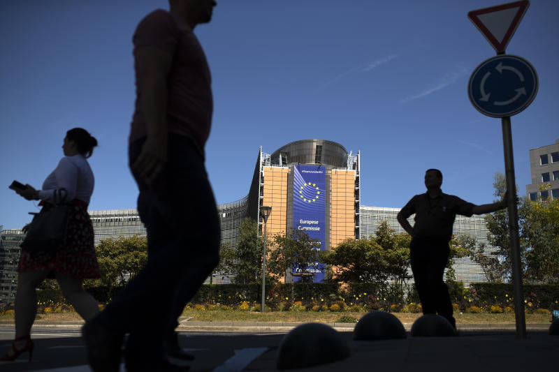 People walk past the European Commission headquarters in Brussels, Tuesday, July 23, 2019. Brexit champion Boris Johnson won the contest to lead Britain's governing Conservative Party on Tuesday and will become the country's next prime minister, tasked with fulfilling his promise to lead the U.K. out of the European Union. (AP Photo/Francisco Seco)