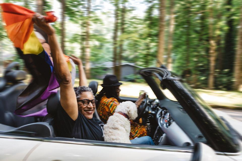 LGBTQ couple flying pride flag in convertible car driving down the road with a dog. Both are people of color, driver is wearing traditional Ghana cloth dress.
