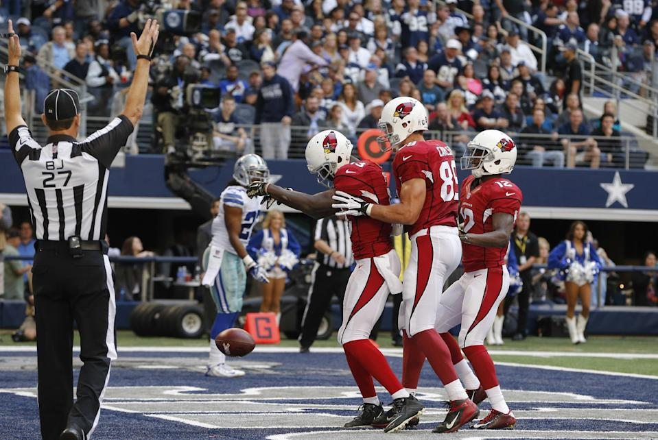 FILE - In this Nov. 2, 2014, file photo, Arizona Cardinals wide receiver Jaron Brown (13) celebrates his touchdown reception against the Dallas Cowboys with tight end John Carlson (89) and wide receiver John Brown (12) during the first half of an NFL football game in Arlington, Texas. (AP Photo/Sue Ogrocki, File)