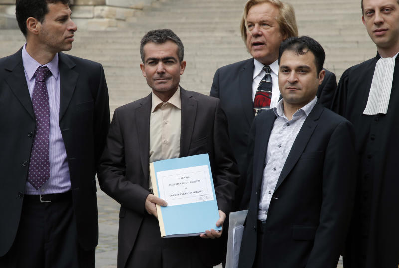 Kamil Abdulqadir Wais Mohammed, center left, shows the file document with Osman Abdulkadir Hassan, center right, framed by their U.S. lawyers, Joaquin Zuckerberg, left, Gavriel Mairone, center rear, and French lawyer David Pere, right, as they arrive at court to file a legal complaint in Paris, Monday, June 10, 2013. Twenty victims of the Saddam Hussein's 1988 chemical weapons attack on the Kurdish town of Halabja are demanding a French judicial investigation into companies that supplied the materials. Halabja marked the deadliest chemical weapons attack against civilians. Saddam suspected the non-Arab Kurds of siding with Iran in the Iran-Iraq war. Up to 5,000 people died in the March 1988 attack. (AP Photo/Francois Mori)