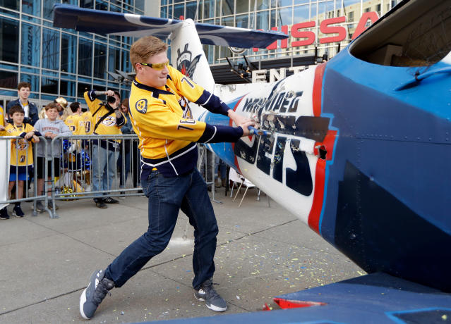 Nashville Predators fan Devin Bradshaw takes a turn beating on a plane painted with the Winnipeg Jets logo and colors outside of Bridgestone Arena before Game 1 of an NHL hockey second-round playoff series between the Predators and the Jets, Friday, April 27, 2018, in Nashville, Tenn. (AP Photo/Mark Humphrey)