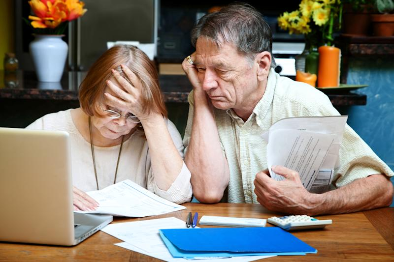 Older man and woman looking at documents worriedly.