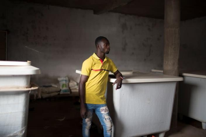 Seydou Sogoba, who works for Amadou Sidibe, walks inside the room where water is piped from underground to the greenhouses and recycled in Katibougou