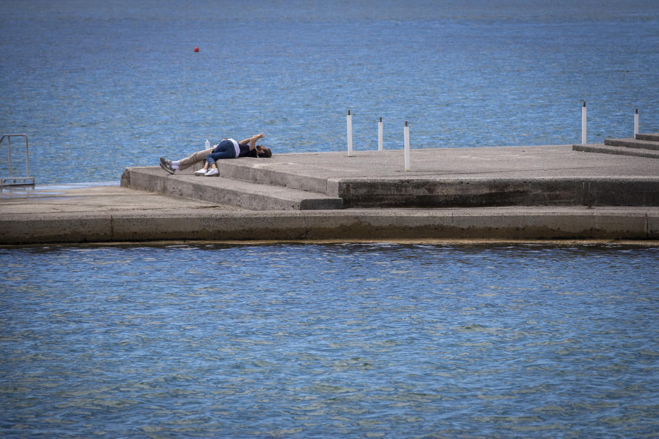 A couple lays at the seafront in Opatija, Croatia, Saturday, May 15, 2021. Croatia has opened its stunning Adriatic coastline for foreign tourists after a year of depressing coronavirus lockdowns and restrictions. (AP Photo/Darko Bandic)
