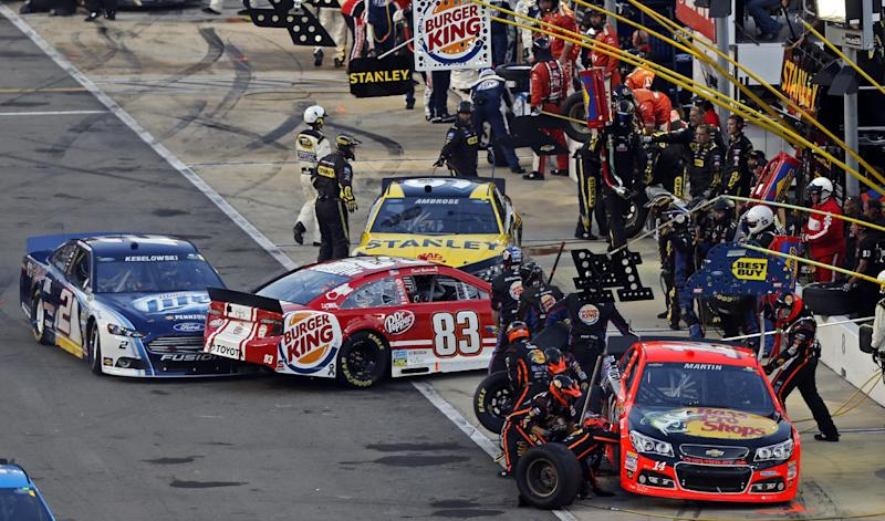 Brad Keselowski (2) spins David Reutimann (83) as Marcos Ambrose (9) tries to get around them during pit stops in the NASCAR Sprint Cup Series auto race, Saturday, Aug. 24, 2013, in Bristol, Tenn. Crew members work on the car of Mark Martin (14). (AP Photo/Wade Payne)