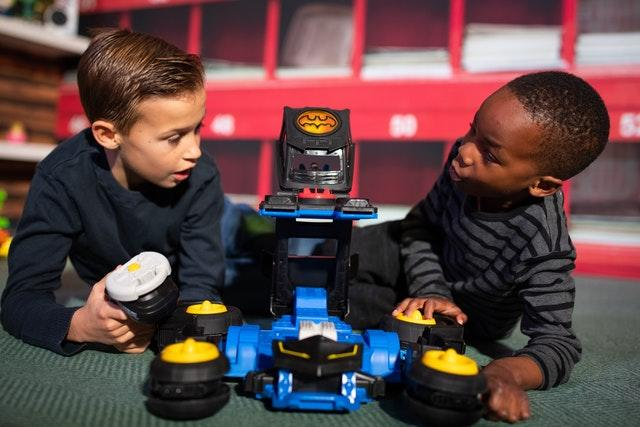 Charlie Bonnet-Davies, 10, and Mofe Akinsanmi, six, play with an Imaginext DC Super Friends Transforming Batmobile