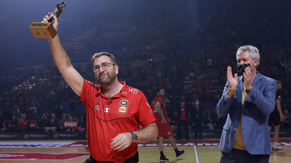 PERTH, AUSTRALIA - JUNE 18: Trevor Gleeson, coach of the Wildcats acknowledges the supporters after being presented the 2021 NBL Coach Of The Year trophy by former Wildcats head coach Alan Black during game one of the NBL Grand Final Series between the Perth Wildcats and Melbourne United at RAC Arena, on June 18, 2021, in Perth, Australia. (Photo by Paul Kane/Getty Images)