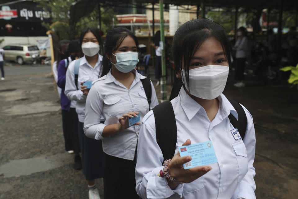 Students show off the COVID-19 vaccination pass before their morning classes at the Preah Sisowath high school, in Phnom Penh, Cambodia, Wednesday, Sept. 15, 2021. The Municipal of Phnom Penh recently issued a statement to reopen junior high and high schools due to the high number of vaccination rates for teachers and students, low infection rates and the schools' to compliance to health standards. (AP Photo/Heng Sinith)