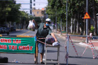 A man picks up food delivery at a checkpoint of a street cordoned off for the lockdown order in Vung Tau, Vietnam Monday, Sept. 6, 2021. Over 20 million Vietnamese students start a new school year on Monday, many of them on virtual classrooms as more than half of the country is in lockdown to contain a COVID-19 surge. (AP Photo/Hau Dinh)
