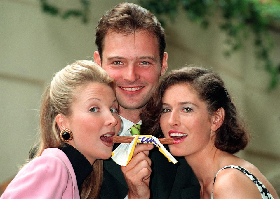 Blue Peter presenter John Leslie with models Kate Charman and Helen Greenwood launching the search for the new Cadbury's Flake girl. (Photo by Tony Harris - PA Images/PA Images via Getty Images)