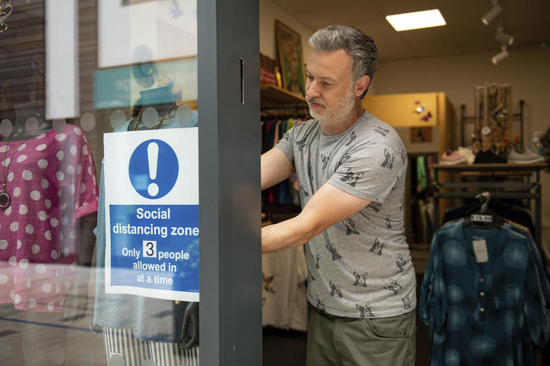 Retailer Clive Williams installs a sign in the window of his Pop Up Clothing Company store, in Stratford-upon-Avon, Warwickshire, England, Sunday, June 14, 2020. Lockdown restrictions are slowly being eased, which should see the economy start to pick up. On Monday, nonessential shops, such as department stores and electronic retailers, can reopen if they can abide by social distancing requirements. (Jacob King/PA via AP)