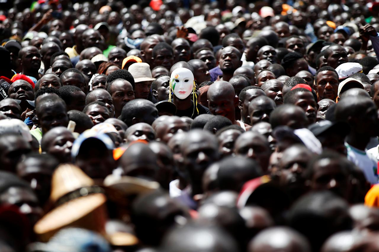 <p>A man wears a mask among fellow supporters as Kenyan opposition leader Raila Odinga (not pictured) takes a symbolic presidential oath of office in Nairobi, Kenya, Jan. 30, 2018. (Photo: Baz Ratner/Reuters) </p>