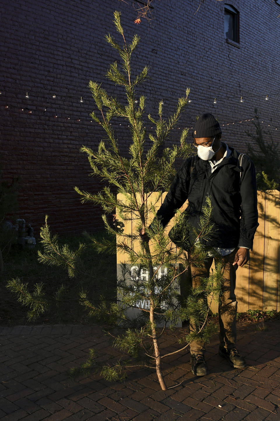 Brian Palmer, of Richmond, holds his recently purchased tree outside of Frank Pichel's tree lot, Sunday, Dec. 6, 2020, in Richmond, Va. A Virginia man has found a way to use Charlie Brown-style Christmas trees to benefit a middle school that provides scholarships for students from an impoverished area. (AP Photo/Will Newton)
