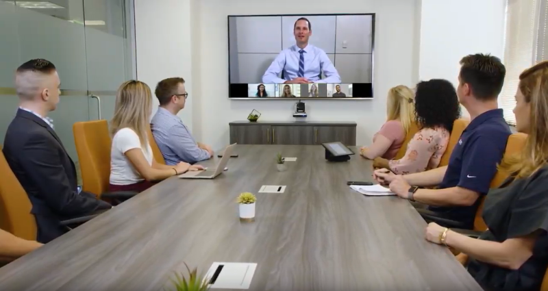 A video-conference call taking place among eight employees, one on a big-screen TV and the others seated at a conference table.
