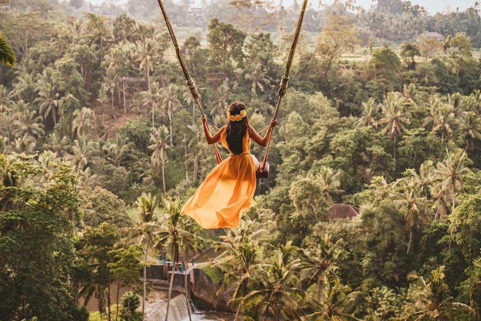 Woman with long swing and forest view in Indonesia