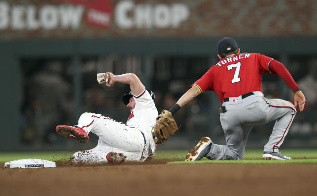 Washington Nationals shortstop Trea Turner, right, tags out Atlanta Braves Matt Joyce on a fielder's choice in the second inning of a baseball game Saturday, Sept. 7, 2019, in Atlanta. (AP Photo/Tami Chappell)