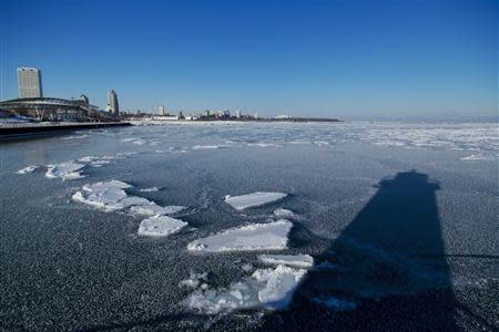 The shadow of a light house is seen in the frozen waters of the port of Milwaukee as another round of arctic air blasts the midwest, keeping the wind chill in the negative numbers, in Milwaukee, Wisconsin February, 6, 2014. REUTERS/Darren Hauck
