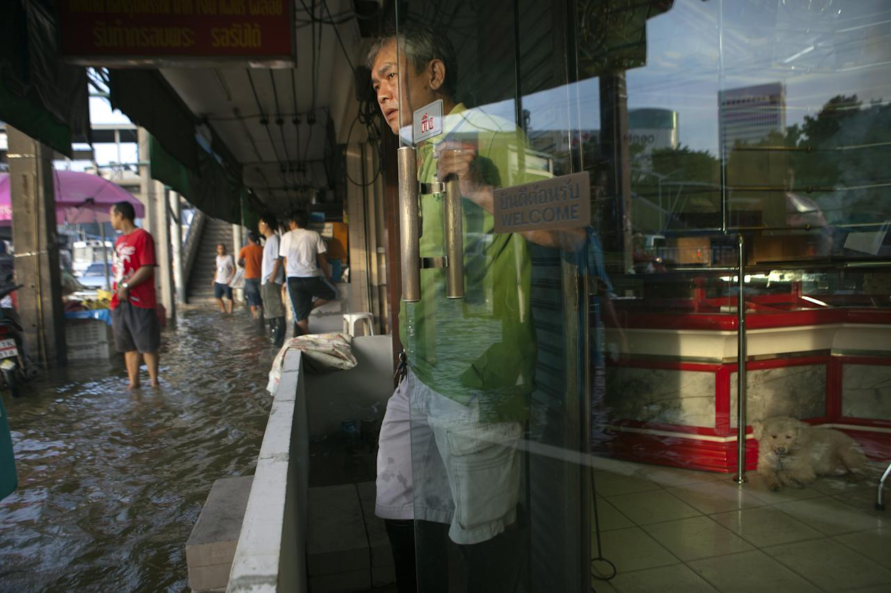 BANGKOK,THAILAND - NOVEMBER 4: A Thai shopkeeper looks out as flood waters take over the streets moving to the Lat Phrao area, a major shopping and business district November 4, 2011 in Bangkok, Thailand. Over seven major industrial parks in Bangkok and, thousands of factories have been closed in the central Thai province of Ayutthaya and Nonthaburi with millions of tons of rice damaged. Thailand is experiencing the worst flooding in over 50 years which has affected more than nine million people. Over 400 people have died in flood-related incidents since late July according to the Department of Disaster Prevention and Mitigation. (Photo by Paula Bronstein/Getty Images)