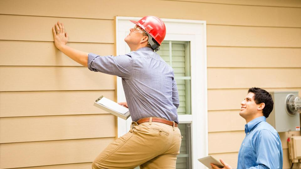 Repairmen, building inspectors, exterminators, engineers, insurance adjusters, or other blue collar workers examine a building/home's exterior wall and foundation.
