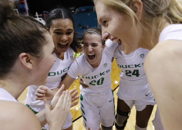 Oregon's Satou Sabally, second from left, Sabrina Ionescu (20), Ruthy Hebard (24) and others celebrate after defeating UCLA in overtime in an NCAA college basketball game in the semifinals of the Pac-12 women's tournament Saturday, March 9, 2019, in Las Vegas. (AP Photo/John Locher)