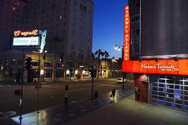 PHOTO: A lone pedestrian passes by Madame Tussauds wax museum on the largely empty Hollywood Boulevard as shutdown orders continue in California due to the coronavirus pandemic, May 11, 2020, in Los Angeles. (Chris Pizzello/AP)