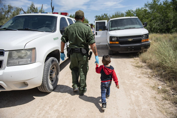 Border Patrol agent Roy Ramirez takes a boy to get water after being detained near McAllen, Texas. (Photo: Sergio Flores for Yahoo News)