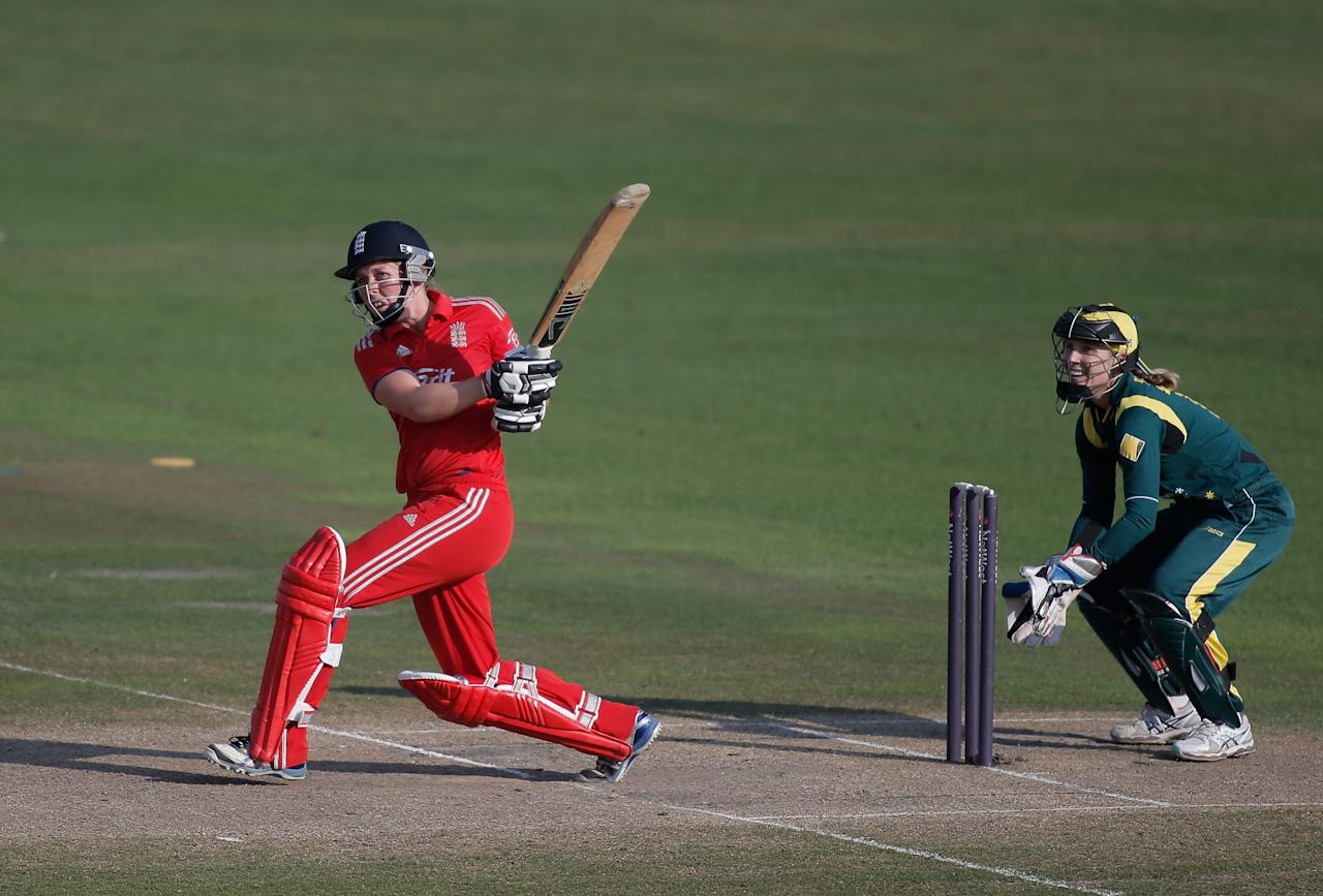 HOVE, ENGLAND - AUGUST 25:  Heather Knight of England hits out watched by Australian wicketkeeper Jodie Fields during the third NatWest One Day International match between England and Australia at the BrightonandHoveJobs.com County Ground on August 25, 2013 in Hove, England.  (Photo by Harry Engels/Getty Images)