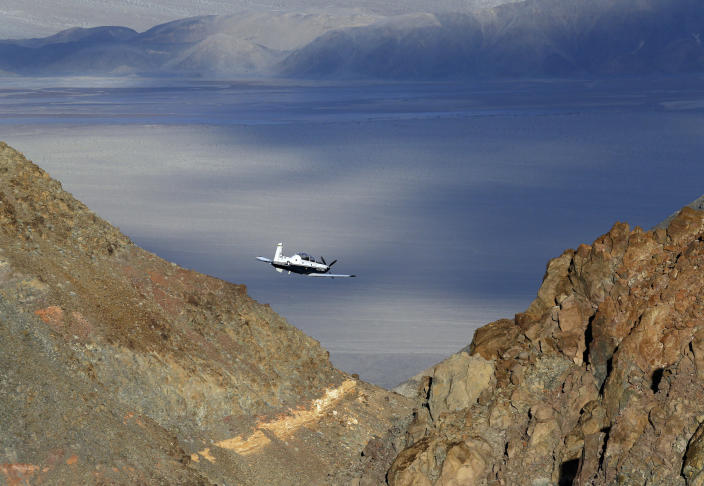 "FILE - In this Feb. 27, 2017 file photo, a Beechcraft T-6 Texan II trainer from Sheppard AFB Texas flies out of what is known as Star Wars Canyon, a rugged area over Death Valley National Park in the California desert that is a training area for military aviators. A U.S. Navy fighter jet crashed Wednesday, July 31, 2019, in the national park, injuring several people who were at the scenic overlook where aviation enthusiasts routinely watch military pilots speeding low through ""Star Wars Canyon,"" officials said. U.S. and foreign militaries train pilots and test jets in the gorge officially called Rainbow Canyon near the park's western entrance. Military flights there date back to World War II. Training flights are almost a daily feature with jets thundering below the rim of the canyon. (AP Photo/Ben Margot, File)"
