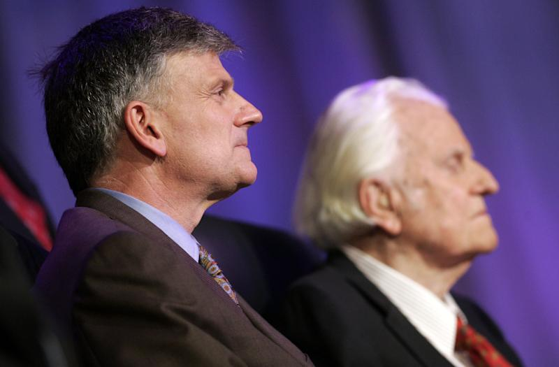 Franklin Graham (L) sits with his father Billy before preaching during the Celebration of Hope on March 12, 2006 in New Orleans, Louisiana.