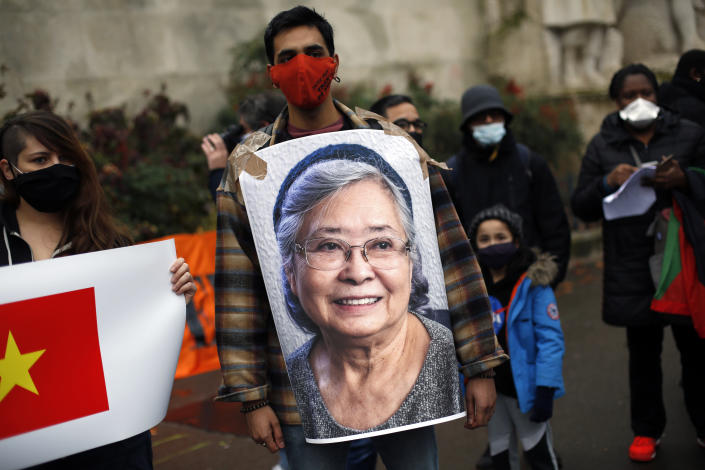 An activist holds a picture of Tran To Nga, a 78-year-old former journalist, during a gathering in support of people exposed to Agent Orange during the Vietnam War, in Paris, Saturday Jan. 30, 2021. Activists gathered Saturday in Paris in support of people exposed to Agent Orange during the Vietnam War, after a French court examined a case opposing a French-Vietnamese woman to 14 companies that produced and sold the toxic chemical. (AP Photo/Thibault Camus)