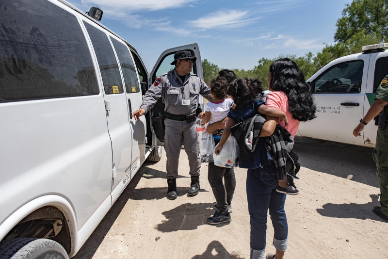 A Border Patrol agent prepares to load a van with illegal immigrants