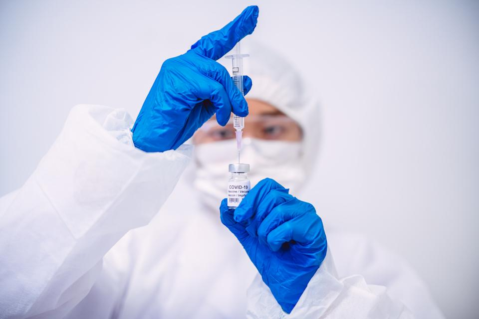 Doctor in protective gloves & workwear filling injection syringe with COVID-19 vaccine.