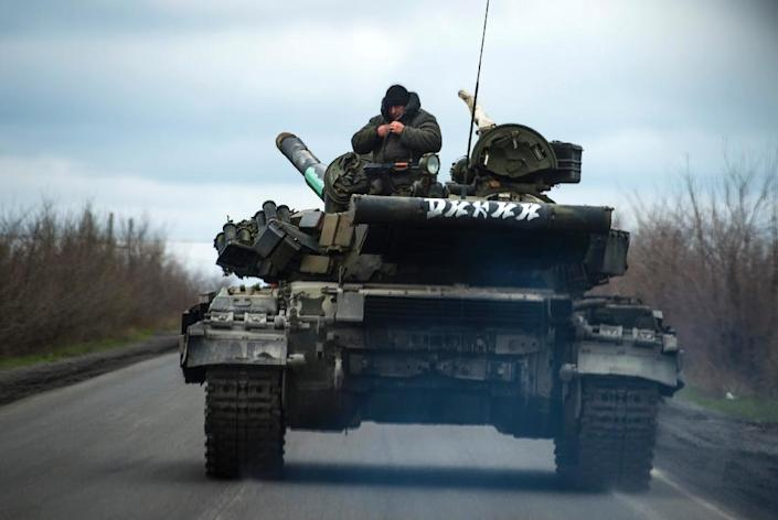 Pro-Russian separatist soldiers stand on their tank as they drive along a road near the village of Kirovske on April 21, 2015 in the self-proclaimed Donetsk People's Republic (AFP Photo/Odd Andersen)