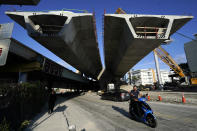 Portions of the new Signature Bridge go up, Friday, May 14, 2021, in the Overtown neighborhood in Miami. At left is the original Interstate 395 bridge built in the 1960's which forced out thousands of residents. (AP Photo/Lynne Sladky)