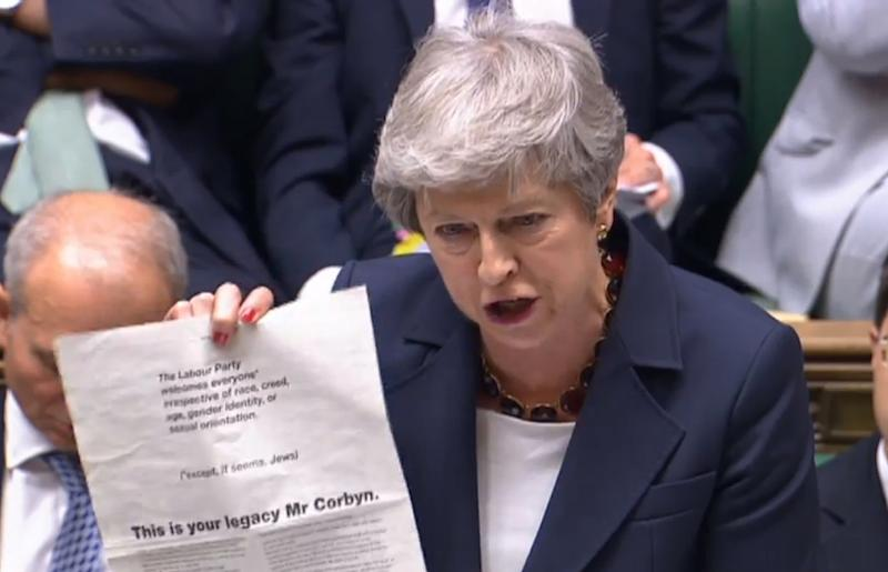 "Prime Minister Theresa May holding up an advert taken from today's Guardian, where more than 60 Labour peers accuse party leader Jeremy Corbyn of ""failing the test of leadership"", during Prime Minister's Questions in the House of Commons, London. PRESS ASSOCIATION Photo. Picture date: Wednesday July 17, 2019. See PA story POLITICS PMQs. Photo credit should read: House of Commons/PA Wire"